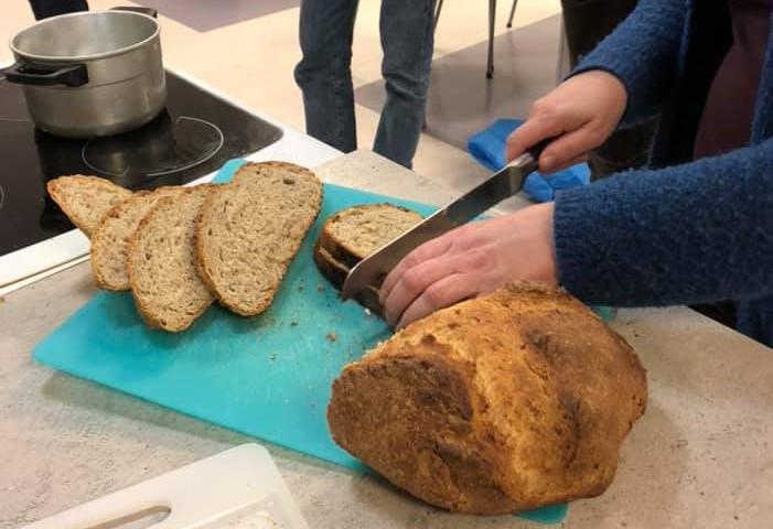 Kvinne skjer opp eit brød.